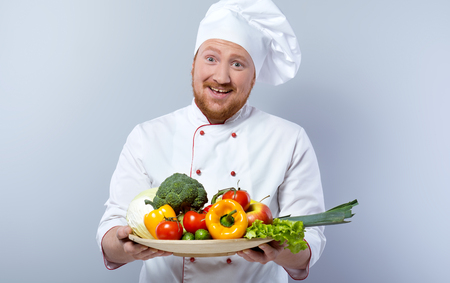 Portrait of positive young male chef in white uniform. Head-cook cheerfully smiling, looking at camera and proposing big plate of fresh vegetables. Standing against grey background Фото со стока