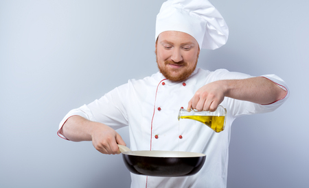 Portrait of positive young male chef in white uniform. Head-cook holding pan and pouring olive oil in it. Standing against grey background
