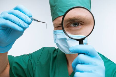 medical mask: Photo of dentist wearing medical mask and gloves. He holding dental instrument and looking at camera through magnifying glass Stock Photo