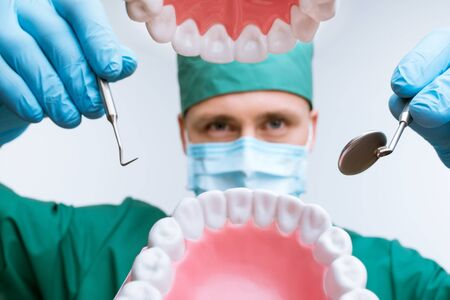 medical mask: Photo of dentist wearing medical mask and gloves. He holding dental instruments. View from the mouth Stock Photo