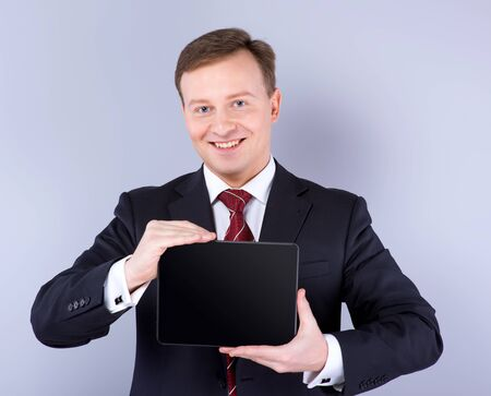 slavonic: Slavonic businessman wearing suit. He looking at camera, smiling and holding tablet computer