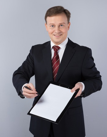 slavonic: Slavonic businessman wearing suit. He looking at camera, smiling and holding documents to sign it