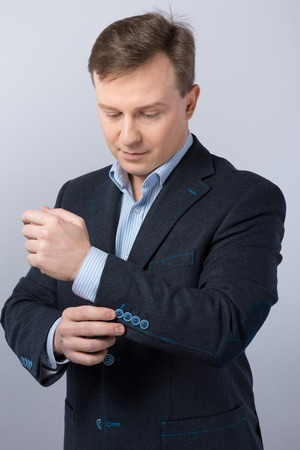 slavonic: Slavonic businessman straightening his suit and looking at it