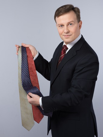 slavonic: Slavonic businessman wearing suit. He looking at camera and choosing ties