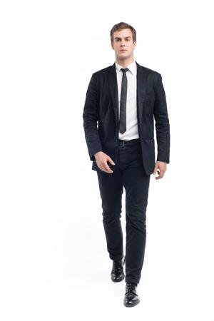 traje formal: Foto del joven empresario vistiendo traje y caminar seriamente hacia la cámara. Aislado en el fondo blanco Foto de archivo