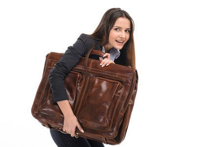 sneaking: Portrait of young businesswoman. She sneaking out with big suitcase. Isolated on white background