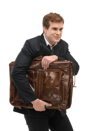 sneaking: Portrait of young businessman. He sneaking out with big suitcase. Isolated on white background Stock Photo