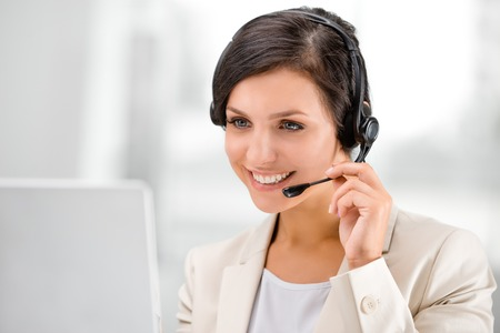 Beautiful smiling woman with headphones using laptop while counseling at call center Stockfoto