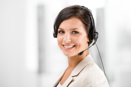 recepcionista: Hermosa mujer sonriente con auriculares mirando a la cámara en la oficina