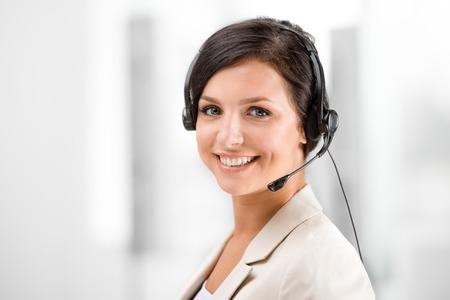 Schöne lächelnde Frau mit den Kopfhörern, die Kamera im Büro
