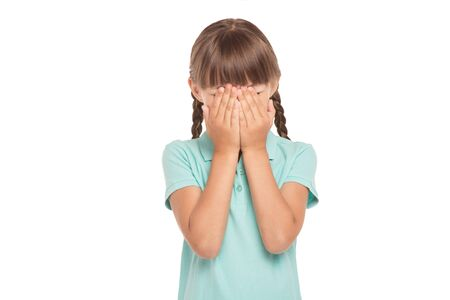 eyes closing: Cute little girl with two braids is isolated on white background. Girl closing her eyes with hands Stock Photo