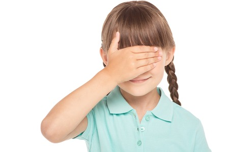 eyes closing: Cute little girl with two braids is isolated on white background. Girl closing her eyes with hand