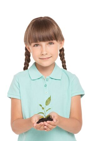 braids: Cute little girl with two braids is isolated on white background. Girl looking at camera, smiling and holding green sprout in hands Stock Photo