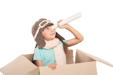 little girl sitting: Cute little girl with two braids is isolated on white background. Girl looking through paper tube, sitting in carton box and wearing like a pilot Stock Photo