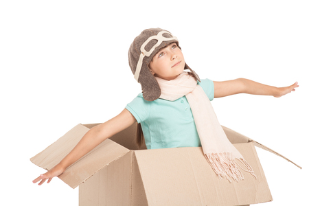 piloto: Niña linda con dos trenzas encuentra aislado en fondo blanco. Muchacha que mira para arriba, sentado en caja de cartón, vestido como un piloto y pretender volar Foto de archivo