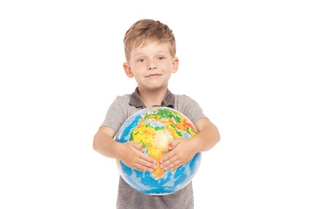 boy little: Cute little boy is isolated on white background. Boy looking at camera, smiling and hugging globe