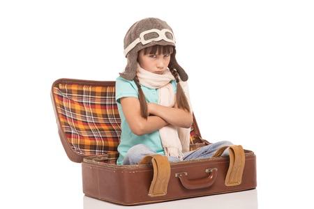 delito: Ni�a linda con dos trenzas encuentra aislado en fondo blanco. Chica Enfadado sentado en la maleta vintage, ofenderse y vistiendo como un piloto