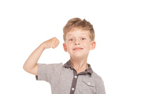 straining: Cute little boy is isolated on white background. Boy looking at camera, showing biceps and arm straining