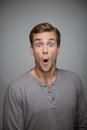 sorpresa: Retrato de hombre joven con estilo hermoso sobre fondo gris. Hombre que mira la cámara con sorpresa