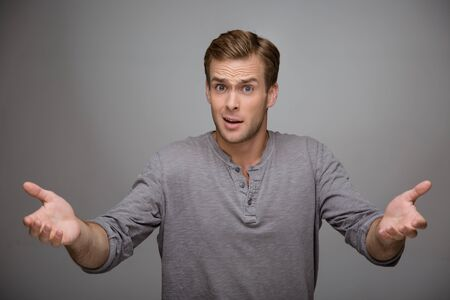 gesticulating: Portrait of handsome stylish young man on grey background. Man gesticulating and looking at camera questioningly