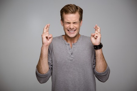 Portrait of handsome stylish young man on grey background. Man praying with his eyes closed and fingers crossed Stock Photo