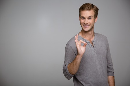 ok sign: Portrait of handsome stylish young man on grey background. Man looking at camera, cheerfully smiling and showing ok sign. Horizontal photo Stock Photo