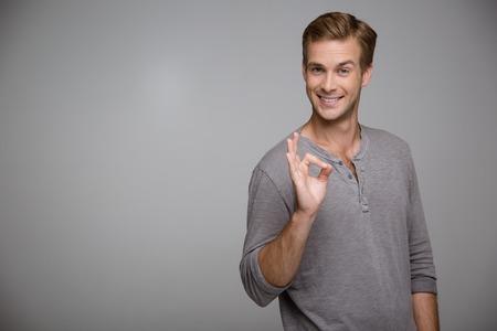 Portret van knappe stijlvolle jonge man op een grijze achtergrond. Man op zoek naar de camera, lacht vrolijk en het tonen van ok teken. horizontale foto Stockfoto