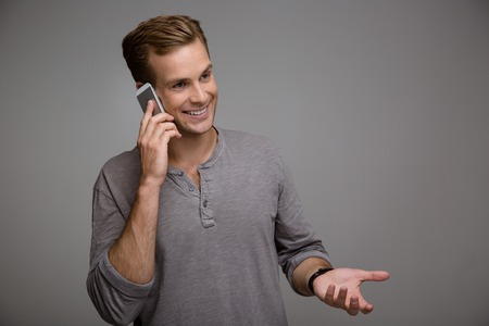 gesticulating: Portrait of handsome stylish young man on grey background. Smiling man using phone and gesticulating Stock Photo