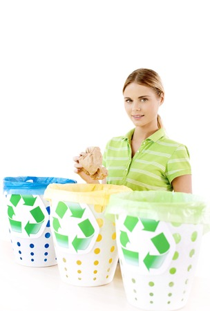 Beautiful young woman standing near three colorful trash cans. Woman sorting rubbish, throwing paper and looking at camera