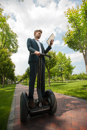 segway: Portrait of handsome young businessman wearing suit. Man using segway and tablet computer