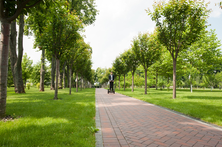 Portrait of handsome young businessman wearing suit. Man using segway. Green alley as background