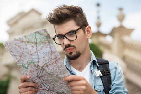bewildered: Portrait of handsome young man on vacation. Bewildered boy looking at map questioningly