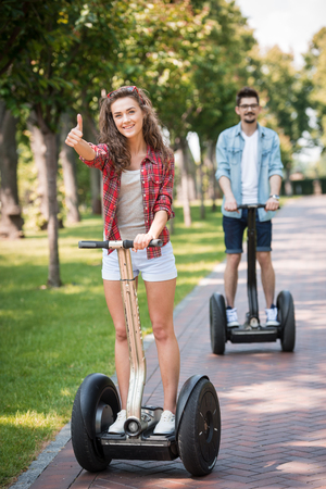 Portrait of beautiful young woman and handsome man. Girl and boy using segway. Girl showing thumb up. Green alley as background