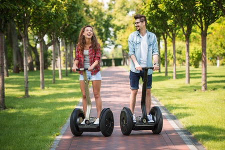 Portrait of beautiful young woman and handsome man. Girl and boy using segway. Girl cheerfully smiling. Green alley as background