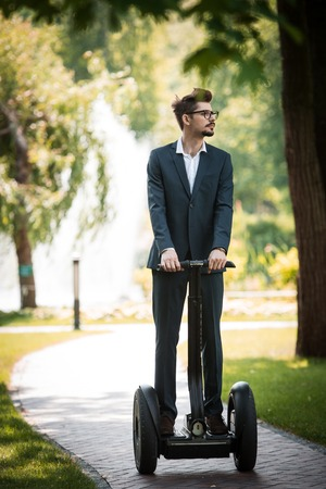 Portrait of handsome young businessman wearing suit. Man using segway and looking aside. Green alley as background Standard-Bild