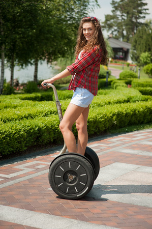 sunshine: Portrait of beautiful young woman. Girl using segway, looking at camera and smiling. Green alley as background