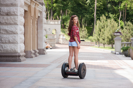 segway: Back view photo of beautiful young woman. Girl using segway, listening to music and smiling