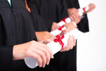 diploma: Cierre de la foto de los estudiantes jóvenes vestidos con togas negras. Aislado en el fondo blanco. Los estudiantes que hayan obtenido títulos