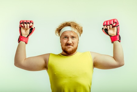 funny picture: Funny picture of red haired, bearded, plump man on white background. Man wearing sportswear and red boxing gloves Stock Photo