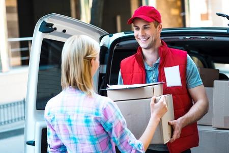Kleurrijke foto van koerier levert een pakket voor de vrouw. Courier lacht. Vrouw accepteert het pakket.