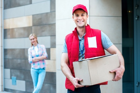 courier man: Colorful picture of courier delivers package for woman. Courier holding the box. Woman stands behind the courier. They are looking at camera and smiling. Stock Photo