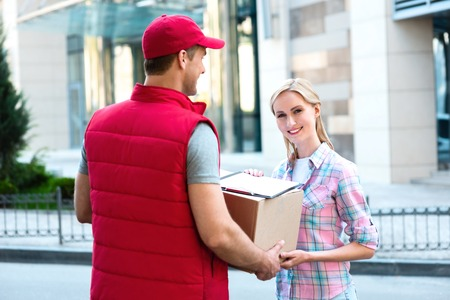 couriers: Colorful picture of courier delivers package for woman. Woman accepts the parcel and smiling.