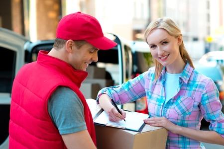 Kleurrijke foto van koerier levert pakket voor vrouw. Vrouw is het ontvangen van het perceel en glimlachen. Stockfoto