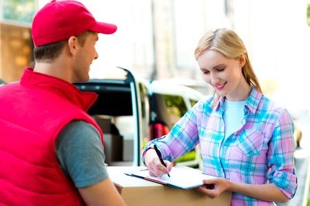 Disegno colorato di corriere consegna pacchetto per donna. La donna sta ricevendo il pacco e sorridente. Archivio Fotografico - 43966358