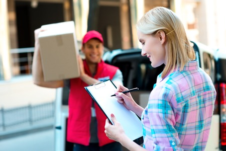 Colorful picture of courier delivers package for woman. Woman is receiving the parcel and smiling. Standard-Bild