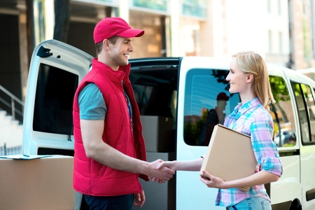 delivers: Colorful picture of courier delivers package for woman. They are shaking hands. Stock Photo