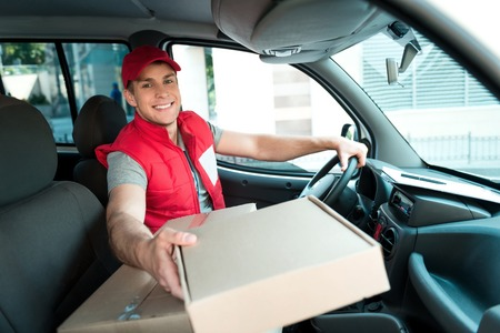 delivers: Colorful picture of courier delivers package. Man is sitting in the car, looking at camera and smiling.