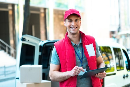 courier: Colorful picture of courier delivers package. Courier holding the box and smiling.
