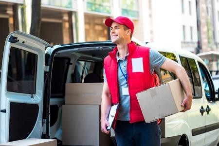 chofer: Cuadro colorido de mensajería entrega del paquete. Courier sosteniendo la caja y sonriendo.