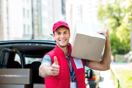 Cuadro colorido de mensajería entrega el paquete para la mujer. Mensajero que sostiene la caja, mirando a la cámara y sonriendo. Foto de archivo